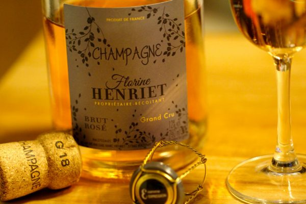 Champagne Florine Henriet Brut Rosé sur table avec bouchon et flutes